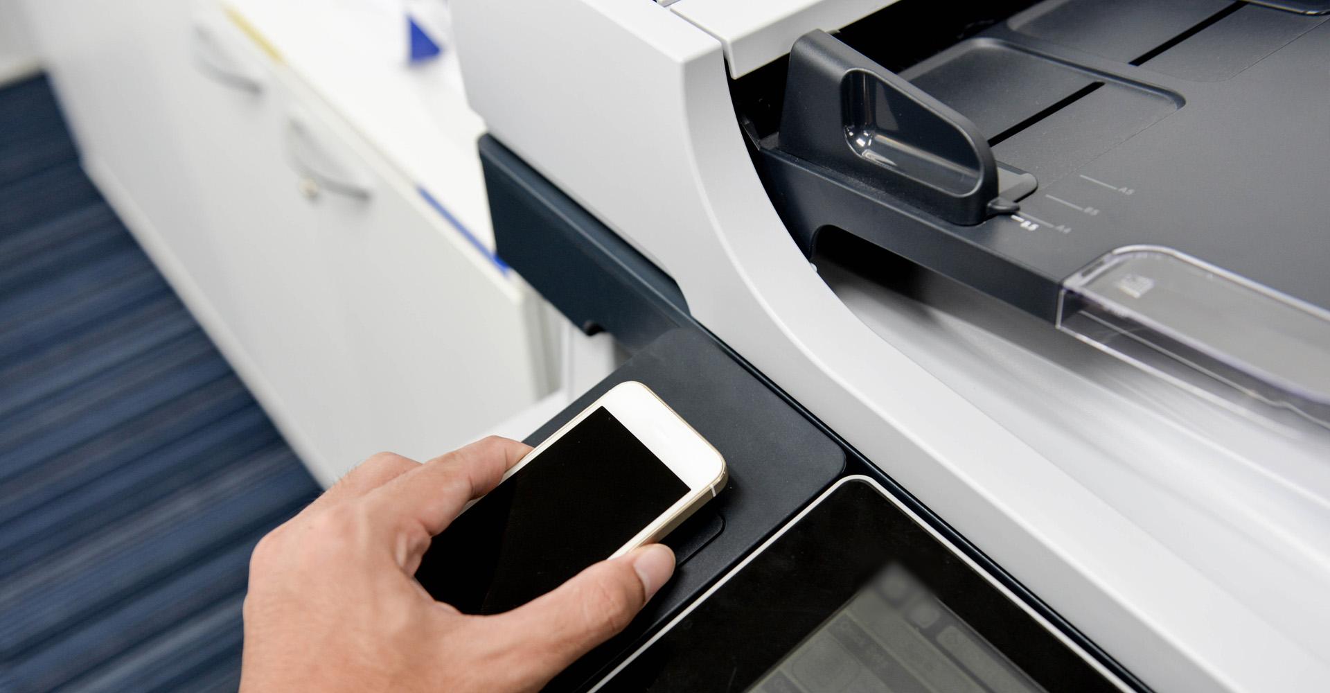 Eine Person legt ein Smartphone auf die entsprechende Ablage eines Druckers um mit diesem per Funk zu drucken