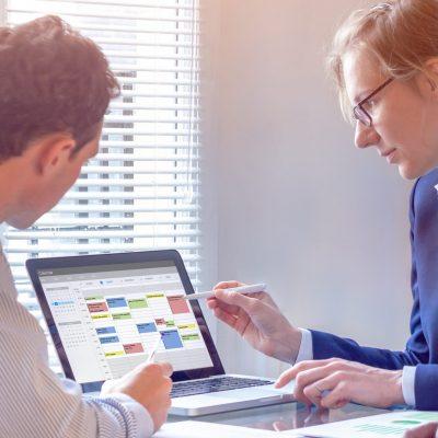 Zwei Männer und eine Frau betrachten den Terminkalender auf einem Notebook.