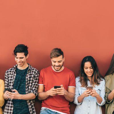 Mehrere junge Menschen stehen vor einer roten Wand und schauen in ihrer Smartphones