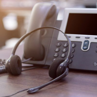 Auf einem Tisch steht ein Telefon und davor liegt ein Headset.