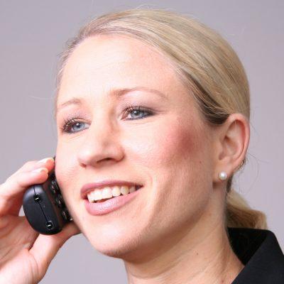 Eine junge Frau telefoniert mit einem schnurlosen Telefon.
