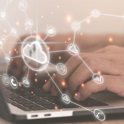 Eine Hand tippt auf einer Notebook-Tastatur und ist von virtuell dargestellten Daten umgeben