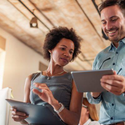 Eine Frau und ein Mann schauen auf einen Tablet-Computer.