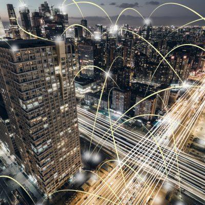 Das Foto zeigt die Luftaufnahme einer Großstadt und symbolische Linien zwischen Gebäuden und Straßen.