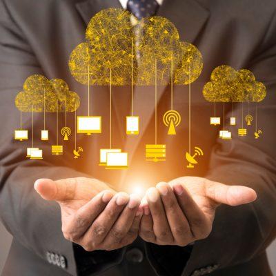 Virtuelle Datenwolken schweben über den geöffneten Händen eines Anzugträgers.