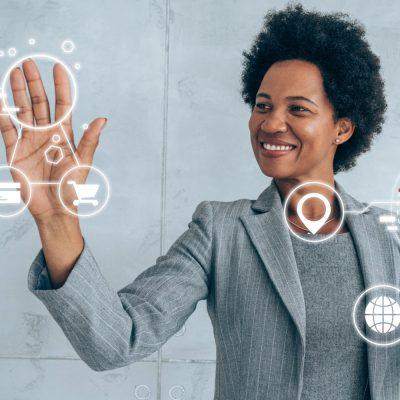Eine Frau im grauen Blazer berührt mit beiden Händen verschiedene virtuelle Symbole.