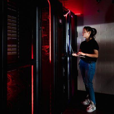 IT-Spezialistin an einem Serverschrank