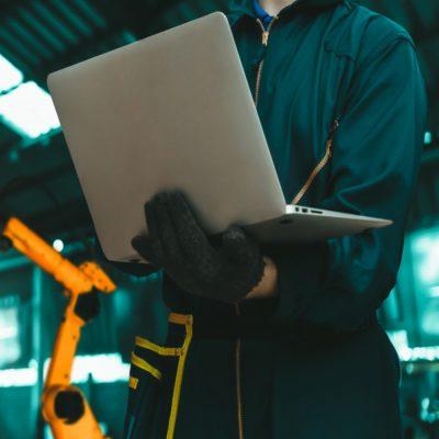 Person, die mit einem Notebook vor Robotern in einer Werkshalle steht.