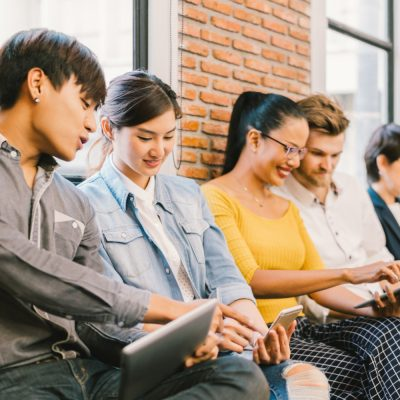 Eine Gruppe junger Menschen sitzt vor einer Mauer, unterhält sich und bedient mobile Endgeräte.