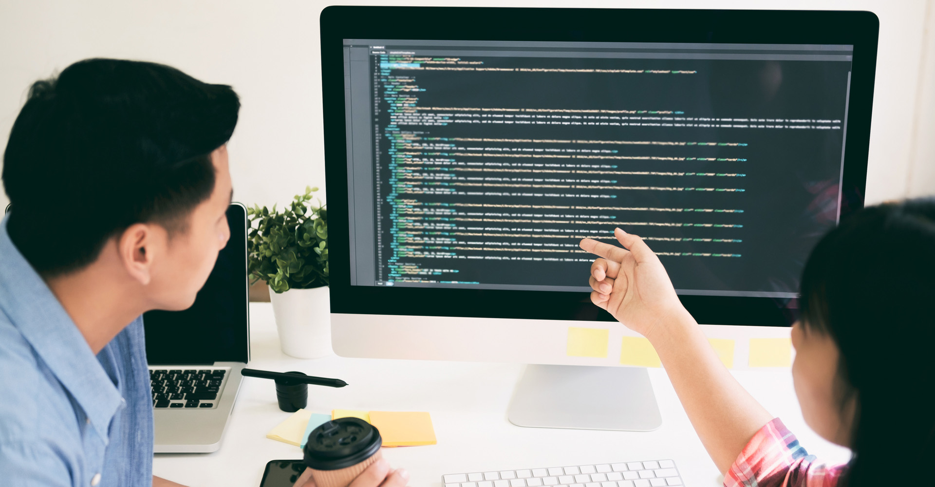 Ein Mann und eine Frau betrachten den Code einer Programmiersprache.