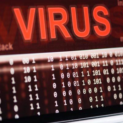 Auf dem Bildschirm eines Notebook erscheint ein roter Virus-Schriftzug.